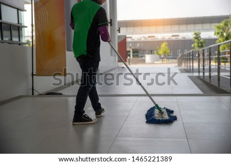 Young Male Janitor Cleaning Floor With Mop on modern building #1465221389