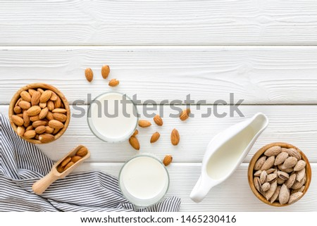 Almond milk in glass with almonds on white wooden background top view copyspace #1465230416
