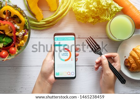Calories counting , diet , food control and weight loss concept. woman using Calorie counter application on her smartphone at dining table with salad, fruit juice, bread and vegetable #1465238459