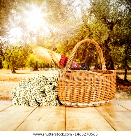 Wooden table background and autumn orchard view in distance. Flowers in baskets and some decoration on the table top.   #1465270565