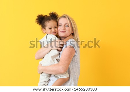 Happy woman with her little African-American daughter on color background #1465280303
