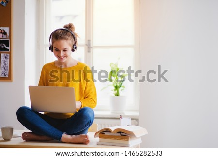 A young female student sitting at the table, using headphones when studying. Royalty-Free Stock Photo #1465282583