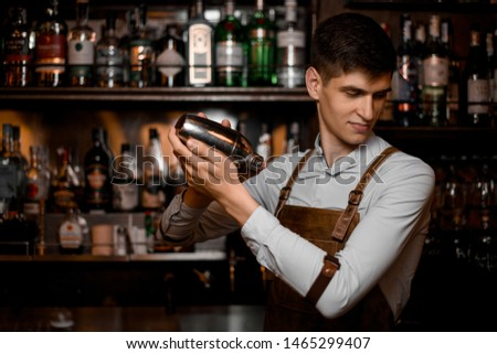 Portrait of young male bartender in leather apron pouring cocktail #1465299407