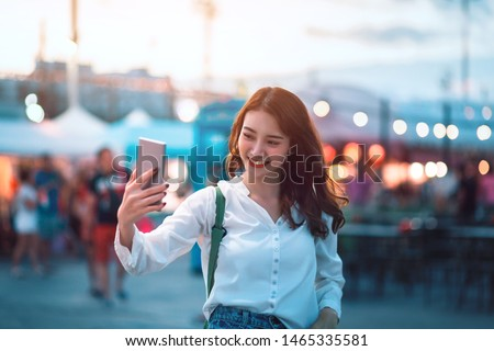 Happy young travel asian woman using mobile phone and selfie on street market against light bokeh background at dusk in Bangkok, Thailand, Travel vacation city concept #1465335581