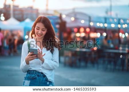 Happy young travel asian woman using mobile phone and relax on street market against light bokeh background at dusk in Bangkok, Thailand, Travel vacation city concept #1465335593