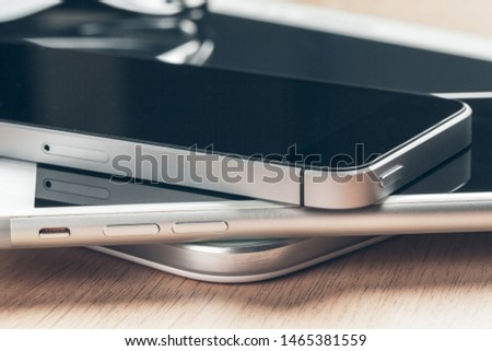 Digital tablet and mobile phone. Electronic devices on wooden table, close up. #1465381559