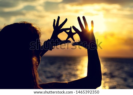 Girl near the sea at sunset with a starfish in the hands. Silhouette photo #1465392350