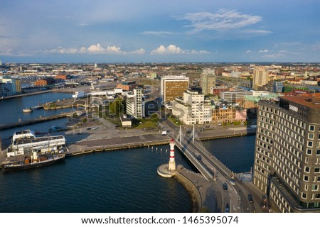 Malmo, Sweden - July 13 2019: Aerial view of the lighthouse and bridge in the harbor of the city, evening time #1465395074