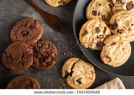 Baked Creamy Dark chocolate chip cookies , Cookie crumble cracks and Brownie chocolate chip cookie on the black dish plated on dark texture background Image using for commercial or menu layout design  #1465404668