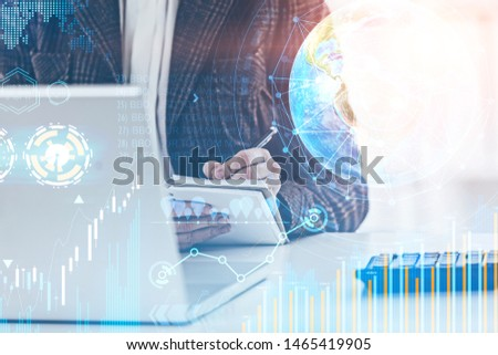 Woman writing in office with double exposure of business infographics and digital interface. Concept of market analysis. Toned image. Elements of this image furnished by NASA #1465419905