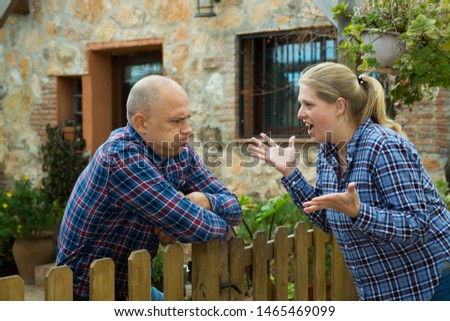 Angry woman quarreling with her male neighbor, talking through wooden fence  #1465469099
