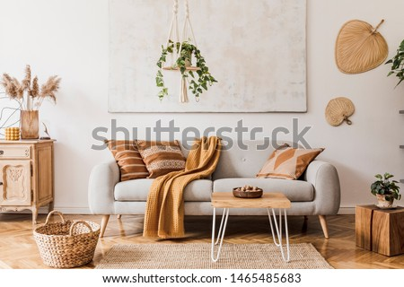 The stylish boho compostion at living room interior with design gray sofa, wooden coffee table, commode and elegant personal accessories. Honey yellow pillow and plaid. Cozy apartment. Home decor #1465485683