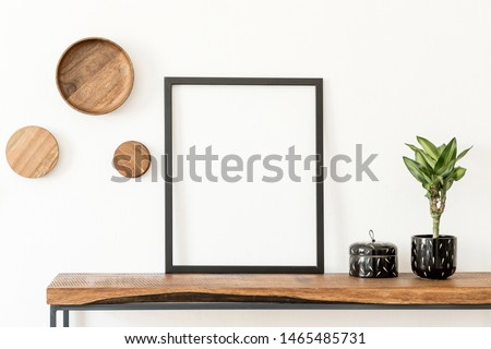 Stylish and cozy scandinavian interior of living room with wooden console, rings on the wall, plants and elegant accessories. Black mock up poster frame. Design home decor. Template. White walls. #1465485731