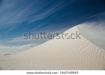 Wide angle view of a young boy and his mother climbing a sand dune at Lancelin Dunes. They are climbing up with sand boards, ready to sandboard down the dune. #1465548869