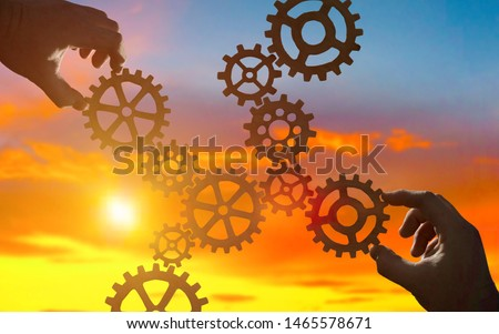 Hands collect gear in a puzzle against the sky in the sunset. Business concept idea, partnership, innovation, teamwork, cooperation #1465578671