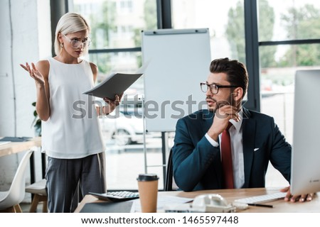 selective focus of emotional blonde businesswoman gesturing while holding folder near handsome man  #1465597448