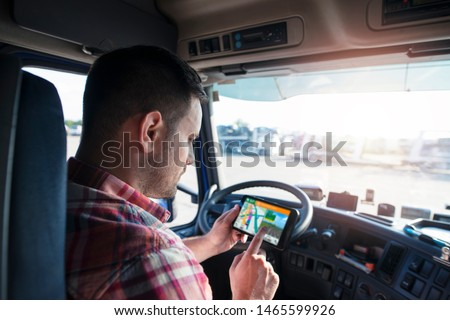 Professional middle aged trucker using truck gps navigation to transport and deliver goods to the destination. Transportation services. #1465599926
