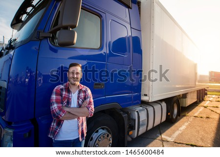 Portrait of middle aged caucasian trucker in casual clothes standing in front of truck long vehicle with trailer. Transportation services. #1465600484