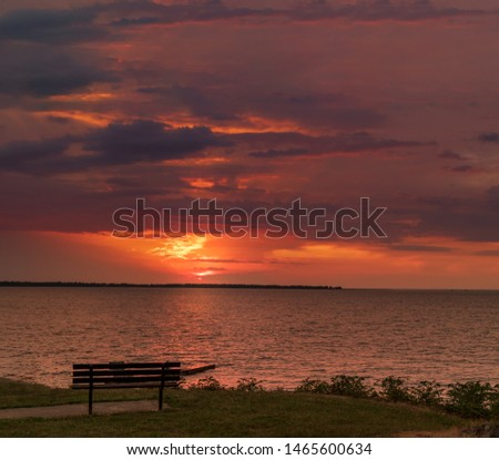 Dramatic orange sky with contrasting clouds view from a park vista epic place to sit and watch the sunset or sunrise  #1465600634