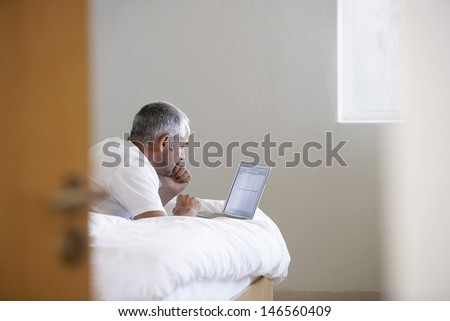 Middle aged man using laptop while lying in bed at home #146560409
