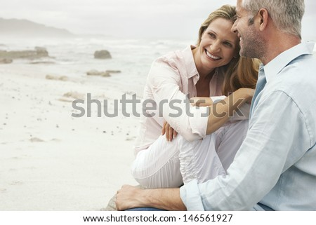 Happy loving couple sitting on beach #146561927