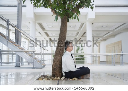 Full length side view of middle aged businessman meditating under tree in office #146568392