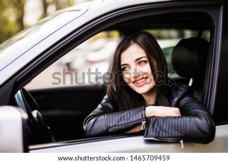 Beautiful girl in jean jacket is smiling while driving a car #1465709459