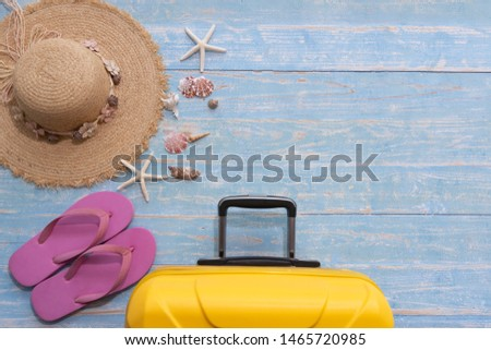 The picture placement the sea concept. Holiday travel. There are hat for woman Shells Starfish sandals and luggage. Blue wooden background