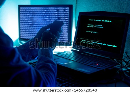 A computer programmer or hacker prints a code on a laptop keyboard to break into a secret organization system. #1465728548