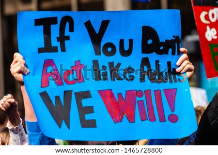 Homemade sign at environmental rally. A colorful poster is seen close-up, held in the hands of an environmentalist, saying if you don't act like adults, we will, during a street demonstration