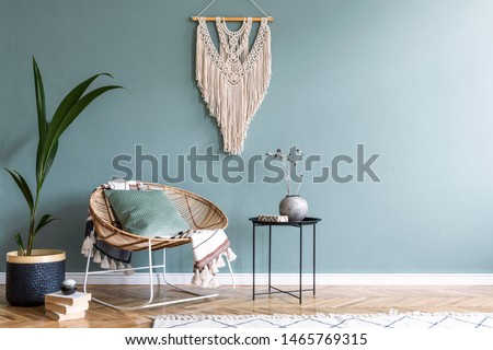 Stylish minimalistic interior of living room with design rattan armchair, black coffee table, tropical platn in basket, beige macrame on the wall and elegant accessories. Eucalyptus color of wall.  #1465769315