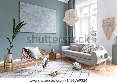 Stylish and design composition of living room with gray sofa, rattan armchair, cube, plaid, pillows, tropical plants, macrame and elegant accessories. Stylish home decor. Bright interior. Template. #1465769324