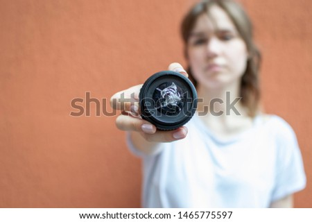girl holds a broken photo lens, the photographer dropped the glass, copy space #1465775597