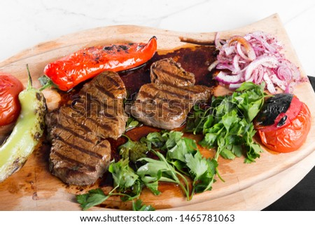 Turkish Traditional Delicious Mutton Beef Steak with vegetables on wood board ready to eat. White marble background. #1465781063