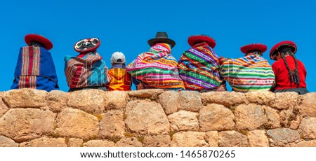 Panoramic photograph of Quechua indigenous women in traditional clothing with a boy sitting on an ancient Inca wall in Chinchero, Cusco Province, Peru. #1465870265