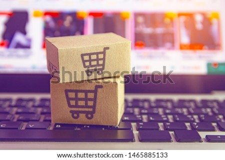 Online shopping - Paper cartons or parcel with a shopping cart logo on a laptop keyboard. Shopping service on The online web and offers home delivery. #1465885133