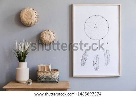 Minimalistic composition of living room interior design with mock up poster frame, flowers in vase, rattan baskets and elegant accessories. Stylish home decor. Template. Gray background walls.