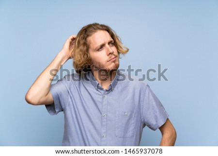 Blonde man over isolated blue wall having doubts and with confuse face expression #1465937078