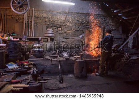 young traditional Blacksmith working with open fire  The blacksmith making flames in smithy with spark fireworks forging hot iron in workshop Royalty-Free Stock Photo #1465955948