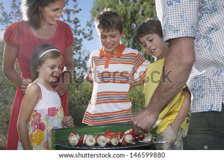 Couple with three children grilling in garden #146599880