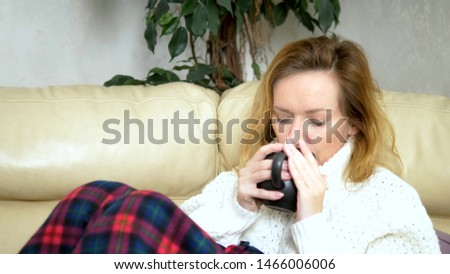 sick woman in a sweater under a blanket drinking a hot drink on the sofa in the living room #1466006006