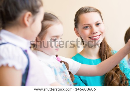 children draw with the teacher in the classroom drawing #146600606