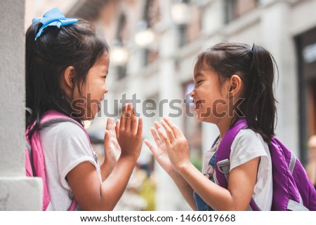 Back to school. Two cute asian child girls with school bag playing together after school in the school #1466019668