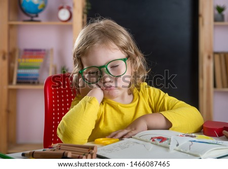 Back to school. Pupil sleeping in class.  Tired little child girl doing homework with head in hands. Hard tusk of reading and writing for elementary school. Boring test in class room.  #1466087465