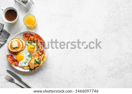 Full American Breakfast on white, top view, copy space. Sunny side fried eggs, roasted bacon, hash brown, pancakes, orange juice and coffee for breakfast. #1466097746