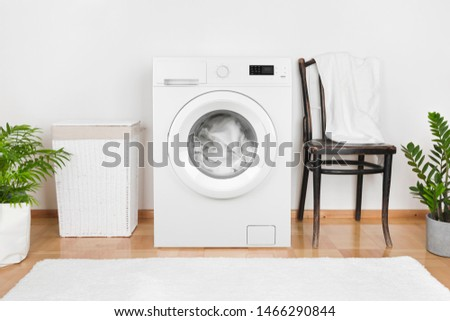 Interior of laundry room with washing machine and laundry basket #1466290844