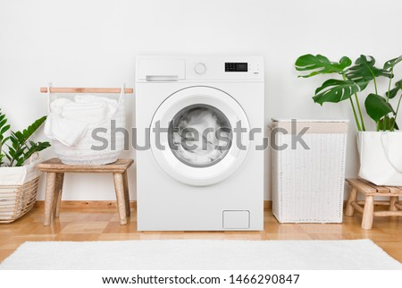Modern washing machine, laundry in baskets and domestic room interior #1466290847