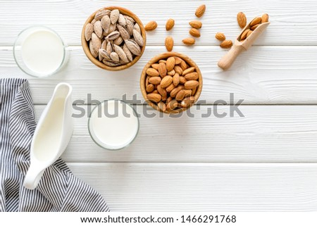 Almond milk in glass with almonds on white wooden background top view copyspace #1466291768