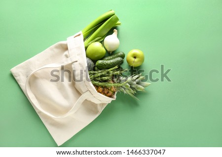 Eco bag with products on color background