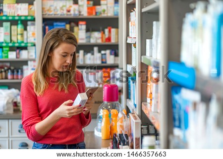 Mid adult female customer choosing product at pharmacy. Everything I need here. Portrait of a beautiful female pharmacy customer. Female customer selecting products in drugstore. #1466357663